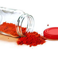A jar of red powder with no lid that has been tipped over